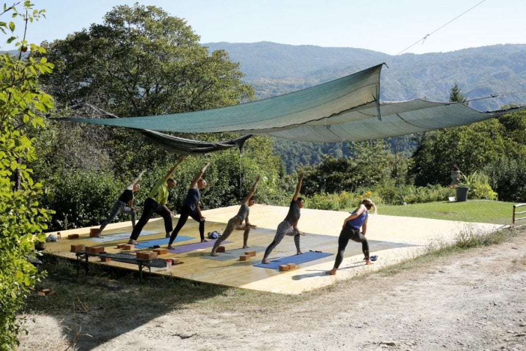Italy Yoga Retreat with Ramila in June 2017 - Yoga session on platform overlooking stunning mountains and greenery
